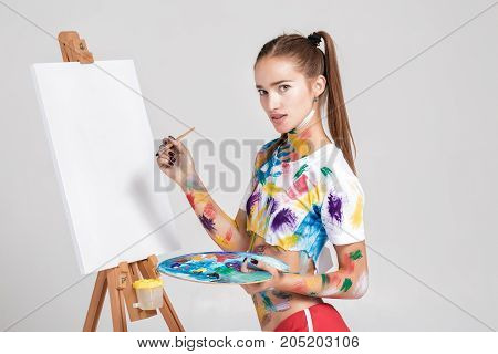 beautiful young woman artist soiled in colorful paint draws on canvas and looks at the camera.