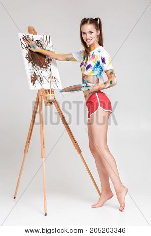 smiling young woman artist soiled in colorful paint draws on canvas. woman smears paint on canvas