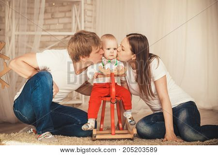 Mom And Dad Kiss Their Little Son