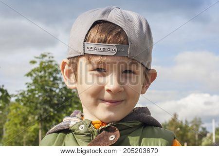 Boy in backward cap smiling during outdoor activity. Portrait of happy kid