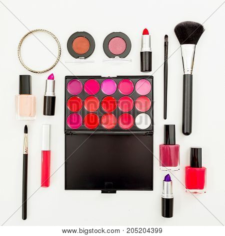 Feminine desk with woman cosmetics - lipstick, nail polish and accessories on white background. Flat lay, top view. Beauty concept