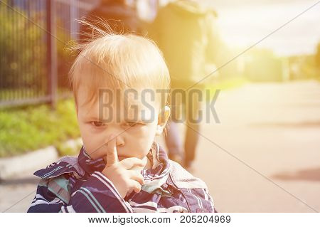 Toddler click on his nose by finger.Sad offended boy dont't want to play outdoor