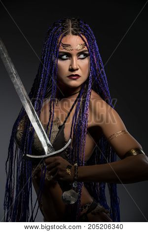 Sexy resolute horsewoman with African braids hairstyle, temporary gold tattoo on her face and bright makeup topless holding a sword in her hand portrait