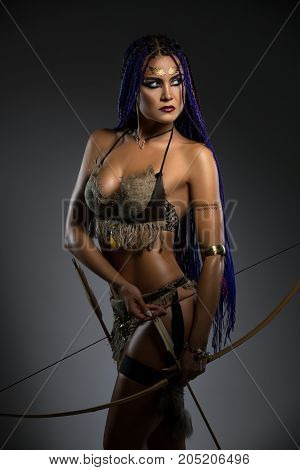 Sexy resolute horsewoman with African braids hairstyle, temporary gold tattoo on her face and bright makeup in leather underwear holding bow and arrows in her hands portrait