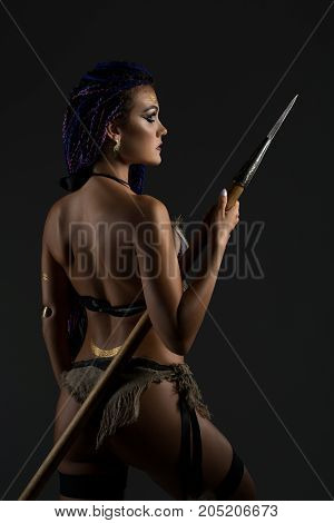 Sexy resolute horsewoman with African braids hairstyle in underwear holding a spear in her hands rearview on gray background