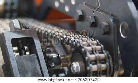 Caterpillar transmission - mechanism of machinery manufacturing on extrusion plant - chemistry industry, close up