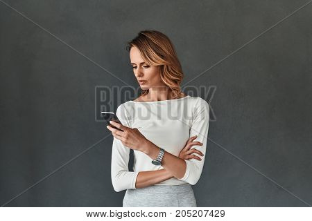 Quick business message. Beautiful young woman in smart casual wear using her smart phone while standing against grey background