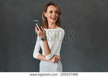 Sharing new ideas. Beautiful young woman in smart casual wear using her smart phone and smiling while standing against grey background