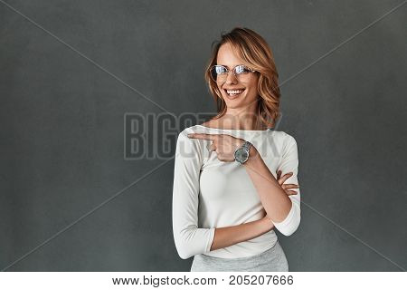 Look over there! Attractive young woman in smart casual wear pointing copy space and smiling while standing against grey background