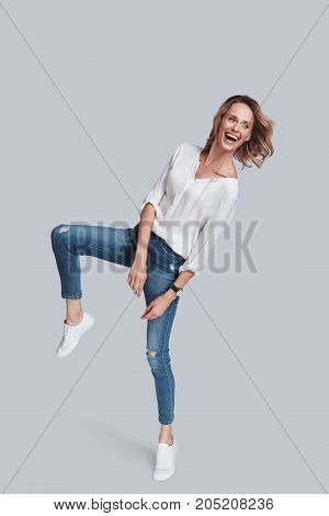 Feeling comfortable in her style. Full length studio shot of attractive young woman in casual wear smiling and looking away while jumping against grey background