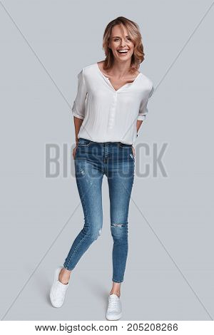 Pure elegance. Full length studio shot of attractive young woman in casual wear smiling and keeping hands in pockets while standing against grey background