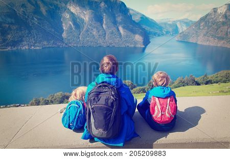 father with two kids travel in Norway looking at fjord