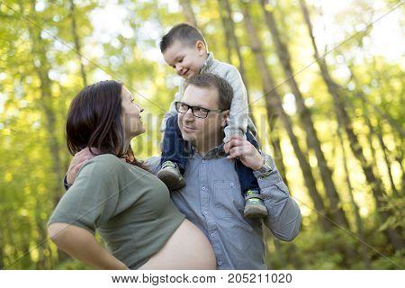 A Happy pregnant family having fun in autumn nature
