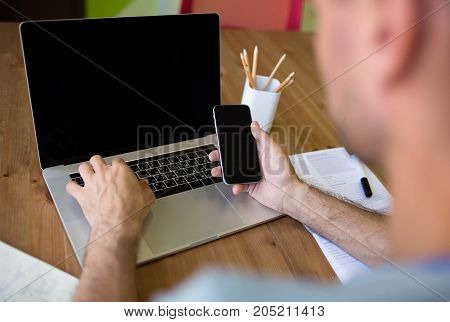 Young man freelancer or blogger working with mobile phone and laptop computer with empty copy space screen . Businessman using cell telephone and net-book sitting in co-working space