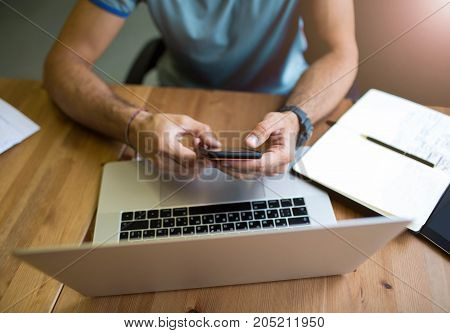 Businessman typing text message on mobile phone, sitting at the table with laptop computer and notebook. Lifestyle writer using cell telephone and net-book