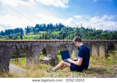 A young handsome man in sunglasses sitting with laptop outdoor and work near old stone railway bridge