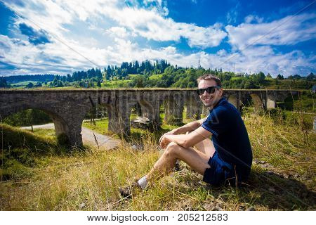 A young handsome man tourist sitting on green hill outdoor near old stone railway bridge