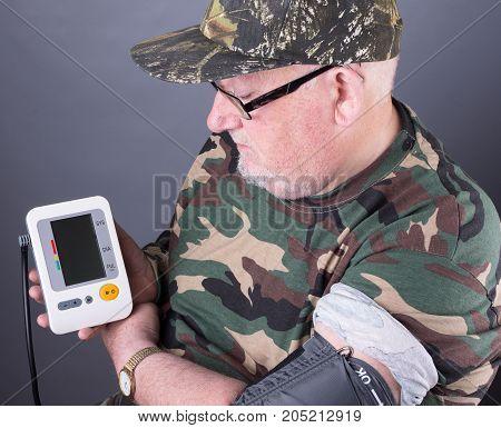 Senior Elderly Man Wearing Camouflage Clothing Checking His Blood Pressure. Blood Pressure Monitor T