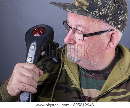 Senior Elderly Man With An Electric Infrared Massager On His Shoulder. Ir Massager Providing Heat An