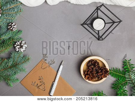Fir branches pine cones and other Christmas assosiated objects on grey background top view