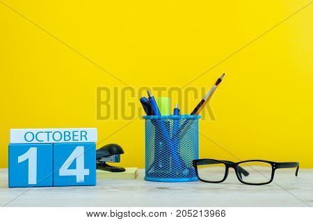 October 14th. Day 14 of october month, wooden color calendar on teacher or student table, yellow background . Autumn time.