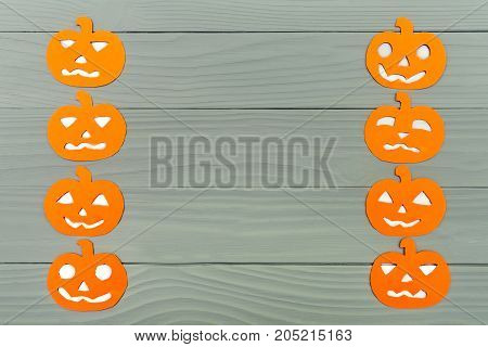 Vertical frame with different pumpkin paper silhouettes on a gray wooden table. Halloween celebration. Copy space for greetings