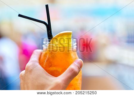 Male Hand Holding Glass With Spirits Spritz Aperol, On A Blurred
