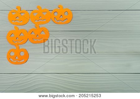 Corner frame on the left side with different pumpkin paper silhouettes on a gray wooden table. Halloween celebration. Copy space for greetings