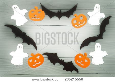 Halloween holiday background made of frame with pumpkins, bats and ghosts cut paper on gray board. Copy space. Light up