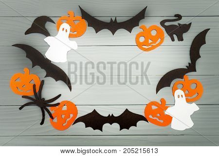 Halloween holiday background made of frame with pumpkins, bats, cat, spider, hat and ghosts cut paper on gray board. Copy space. Light up