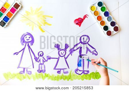 The top view of the child's hand paints a sketch of the family with brush of watercolor on a white sheet of paper