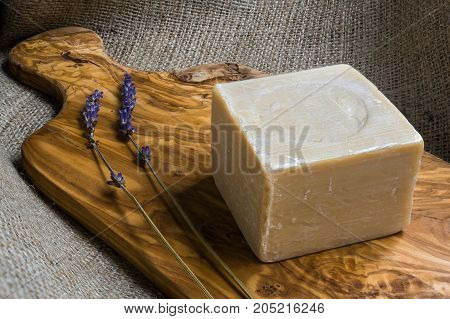 Handmade olive oil soap with a small branch of lavender on wooden chopping board and sackcloth