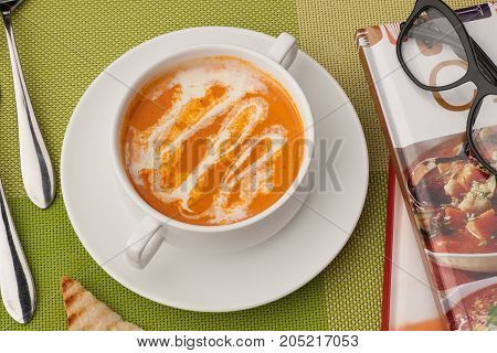 Soup And A Book On A Green Tablecloth