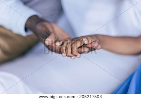 partial view of african american father and son holding hands together