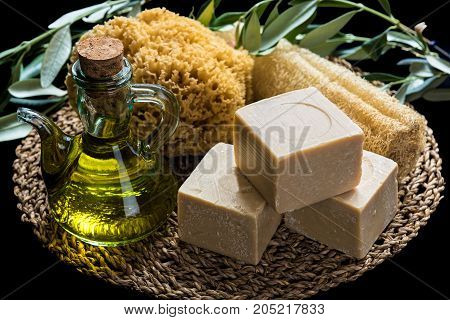 Handmade olive oil soaps together with two natural sea sponges and a bottle of olive oil on natural matting