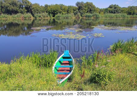 The picture was taken in Ukraine on the South Bug river. In the picture a fishing boat moored to the river bank. In the background another bank of the river is visible. The banks are overgrown with vegetation. The blue sky is reflected in the river.