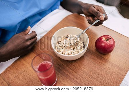 cropped shot of african american man holding spoon during breakfast