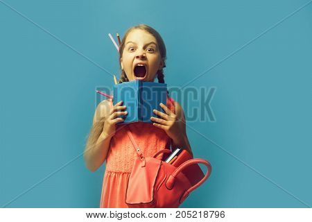 Back to school and childhood concept. Kid with scared screaming face and colored pencils in hair. Pupil with long braids isolated on blue background. Girl with pink bag holds open blue notebook