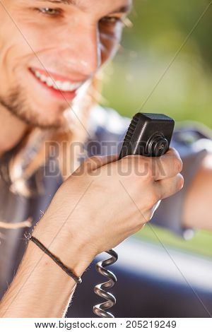Comunication talking while drive auto walkie talkie concept. Young man driving car using cb radio having fun