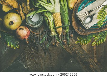 Fall table setting for Thanksgiving day. Flat-lay of plate, cutlery, candle, Autumn harvest vegetables, fruit and fallen yellow leaves for decor over rustic wooden background, top view, copy space