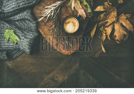Autumn or Fall motning coffee concept. Flat-lay of arm knitted woolen grey sweater, wooden tray, mug of coffee and yellow fallen leaves over dark rustic wooden table background, top view, copy space.