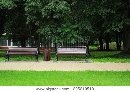 Two stylish brown benches in the old park