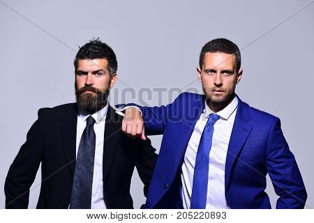 Company leaders rely on each other. Board of executives show friendship and teamwork. Businessmen with serious faces in formal suits on grey background. Business success and cooperation concept