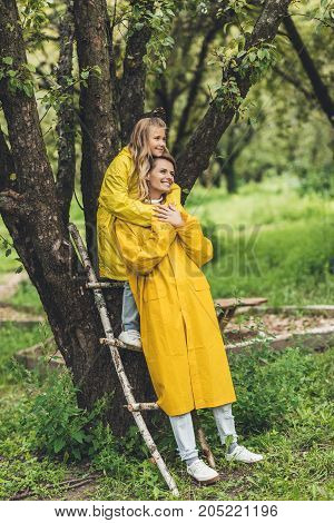 Mother And Daughter In Raincoats At Tree