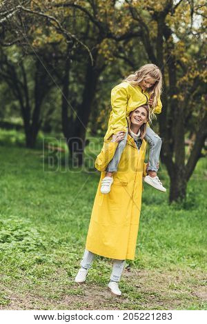 Mother And Daughter In Raincoats At Countryside