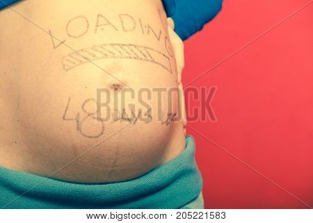 Parenthood waiting for baby concept. Pregnant woman big belly with loading drawing