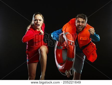 Lifeguards with rescue ring buoy lifebuoy and life vest jacket looking running to accident. Man and woman supervising swimming pool on black.
