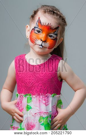 beautiful little girl with a painted fox on her face. face painting