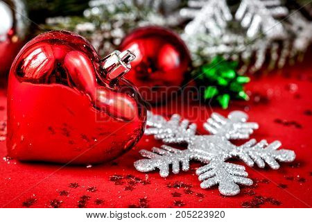 Christmas toys and spruce branches on red background close up.
