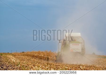 ZRENJANIN SERBIA - SEPTEMBER 19 2017: Claas combine harvester working on corn field. Lower maize crop yield expected this year in Vojvodina region due to drought during summer.